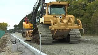 Volvo ECR 235EL  och  CAT D6 Bulldozer jämnar till för att lägga asfalt på  en ny väg