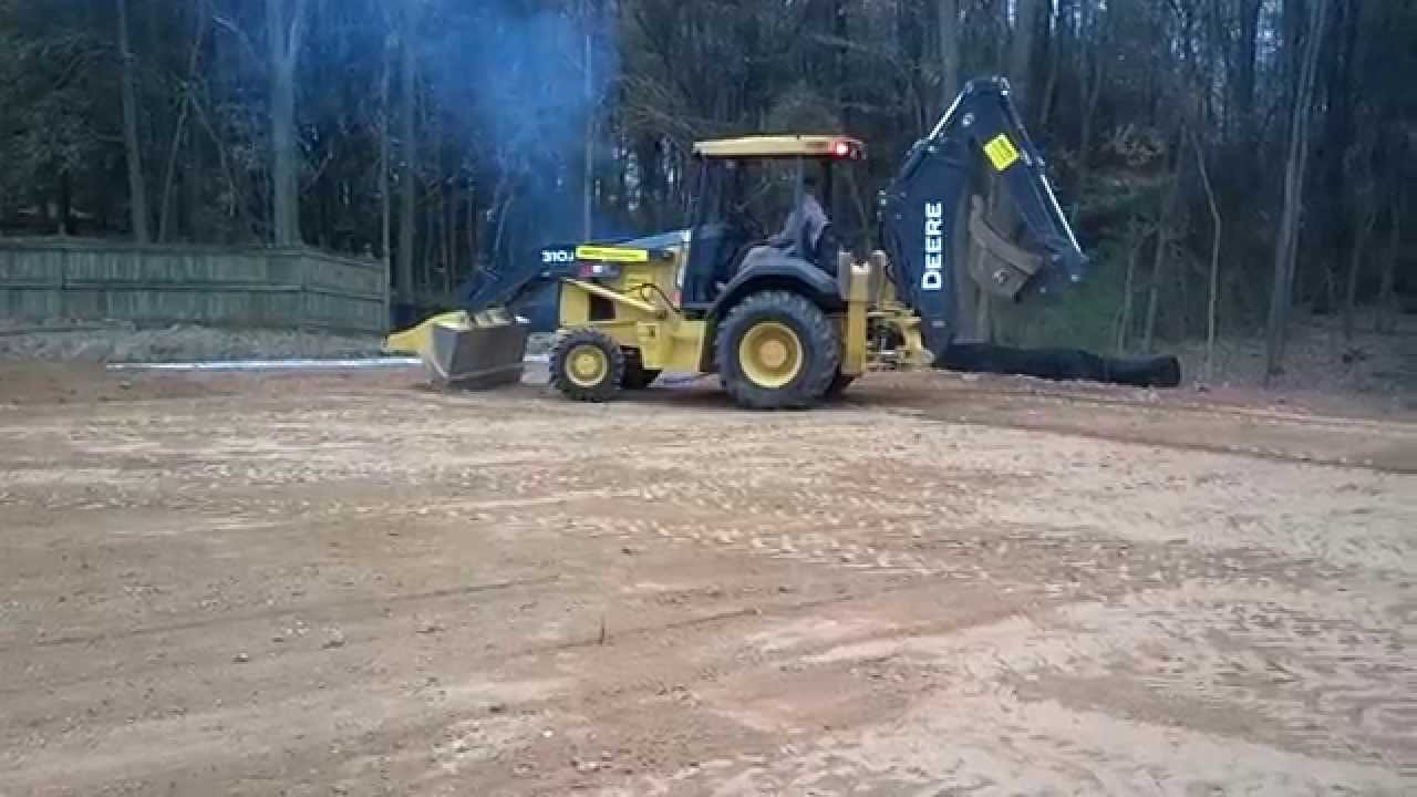 Parking lot grading with backhoe