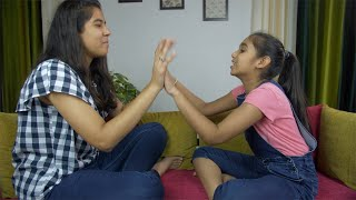 Younger and older sisters playing hand-clapping games while sitting on a sofa
