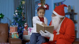 Pretty Indian girl reading a storybook with Santa Claus during Christmas night at home