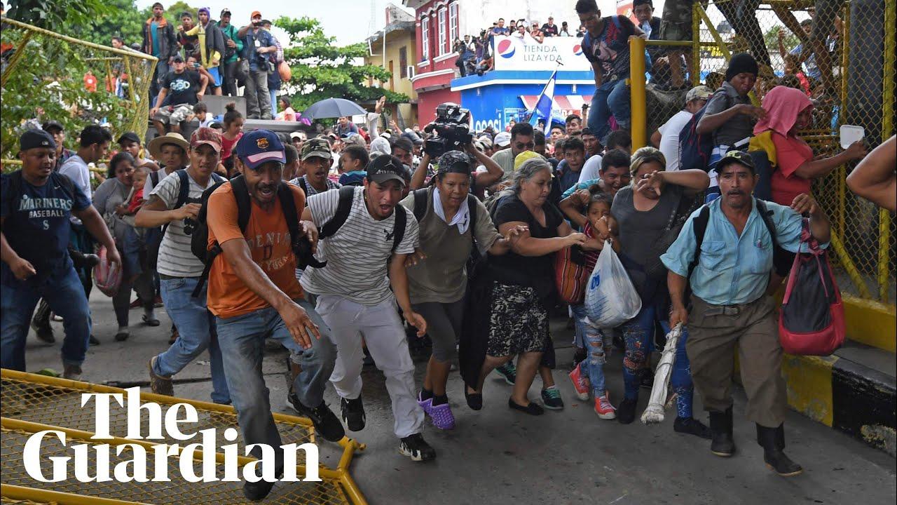 Migrant caravan in Guatemala breaks through border fence into Mexico – video