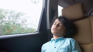 Young innocent boy sleeping at the back seat of a car while traveling home