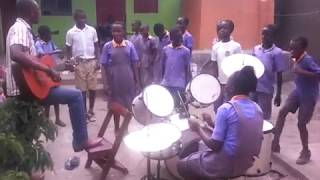 Music lessons at the Bizoha School, a female music pupil hits the drums