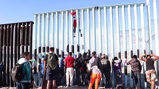 Immigrants climb over U.S. Mexico border wall