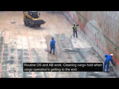 OS AB working in cargo hold. Sweeping cargo residues. Cargo ship. Life at sea. Моряк в трюме