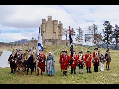 Alan Breck's Regiment re-enactment group march through village to Braemar Castle, Scotland