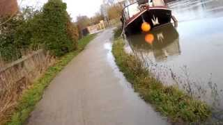 Cycling along flooded towpath on Thames/Isis near Iffley Lock, Oxford