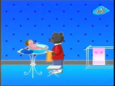 Бурый медвежонок играет с куклой