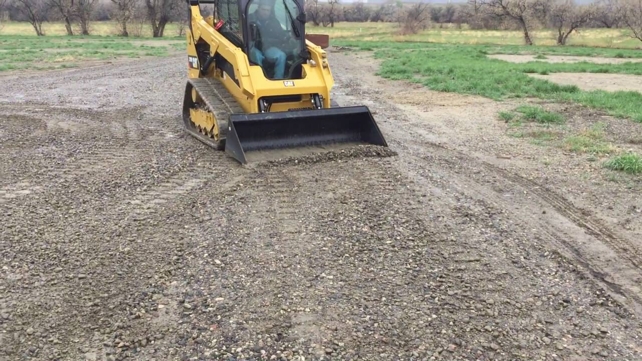 Dolar Excavation Billings Grading a gravel driveway with a cat 259d skid  steer