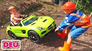 Nikita fährt mit einem Kinderauto und bleibt im Boden stecken. Vlad schleppt ihn mit dem Traktor ab