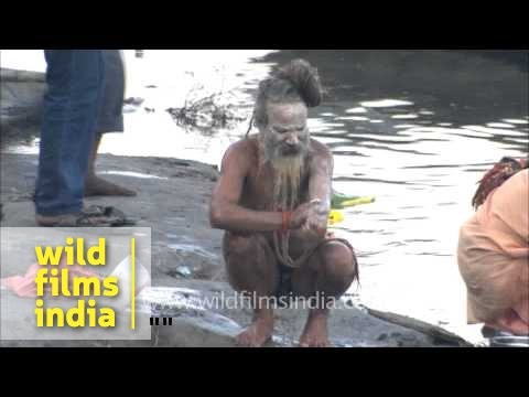 Naga sadhu smears his body with ash after bathing in Ganges at Varanasi
