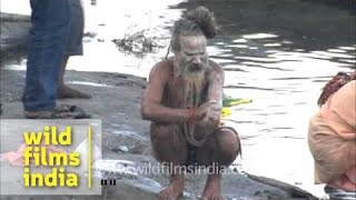 Repeat youtube video A naga sadhu smears his body with ash after bathing in the River Ganges at Varanasi