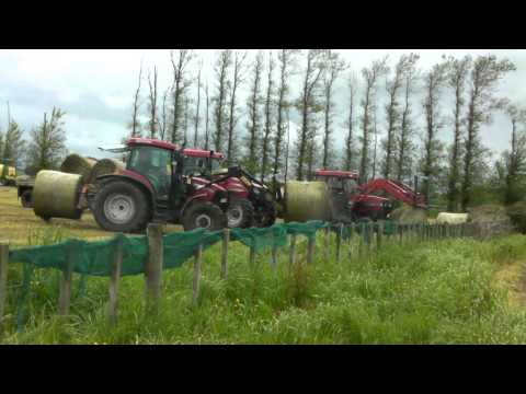 Two Tractor's loading hay on a Trailer