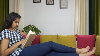 Beautiful Indian girl spending leisure time at home and reading her favorite novel
