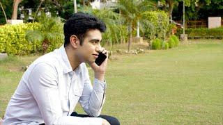 Handsome Indian guy calling someone from his smartphone while sitting in a park