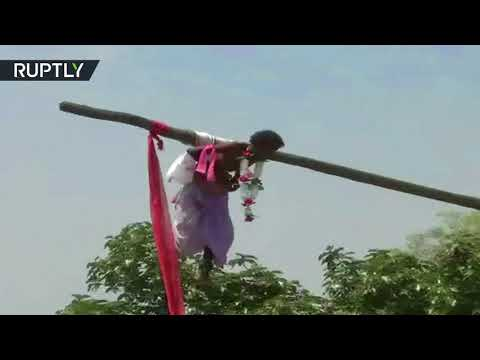 Worshippers pierce skin and hang themselves on hooks to honor Shiva in India (DISTURBING)