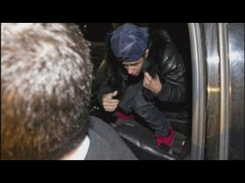 Justin Bieber arrives at a Toronto police station, charged with assaulting limo driver