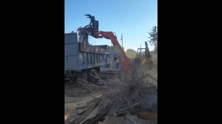 Loading dump truck with compact track loader