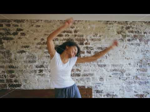 Curly african american young joyful girl have fun dancing on bed at home