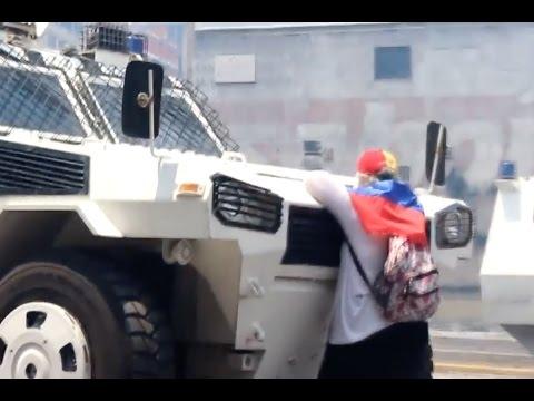 Mujer venezolana parada frente a tanqueta militar en Caracas, símbolo de la protesta