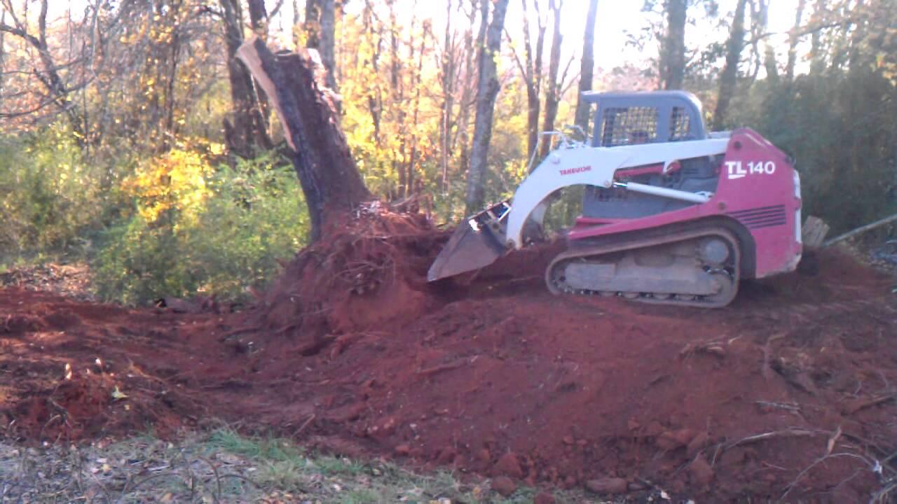 Takeuchi tl 140 pushing up a large stump