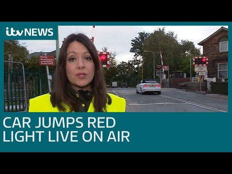 Car jumps red light at level crossing live on air | ITV News