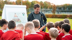 Thomas Müller überrascht Nachwuchs-Kicker im Fußball-Camp mit REWE Inhalten zu gesunder Ernährung.