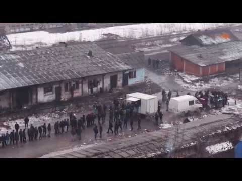 Hundreds of freezing refugees and migrants wait for food in Belgrade - drone video