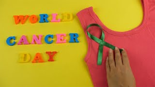 Closeup shot of woman hands putting a green cancer ribbon on a pink tank top
