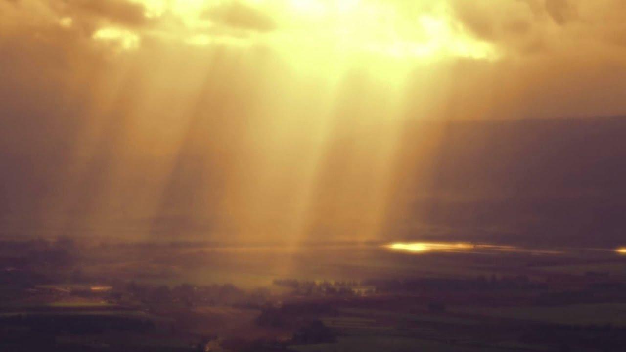 Panning shot of Sun rays illuminating a valley through ...