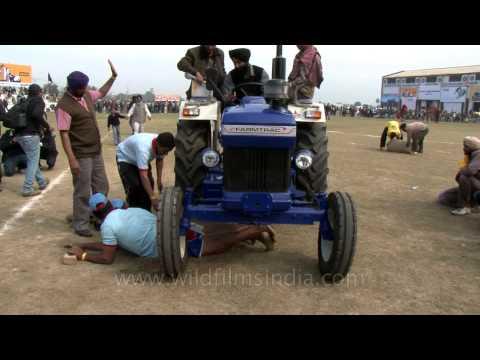 Tractor torture - men going under massive tractor wheels!