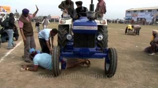 Tractor torture - men going under massive tractor wheels!