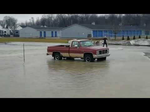 Man Surfs a Flooded Parking Lot in Shipshewana, Indiana