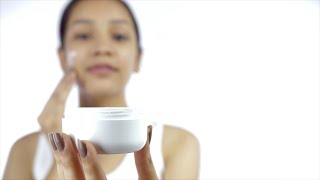 Closeup shot of a happy girl applying moisturizer on her face with a jar in focus - Skin Care