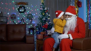 Happy Indian kid in Santa hat sharing his secrets with Santa Claus - Christmas Eve