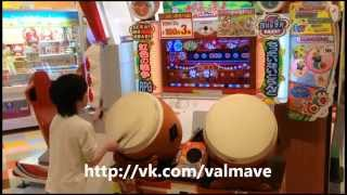 Japanese kid playing on Taiko drums in arcade