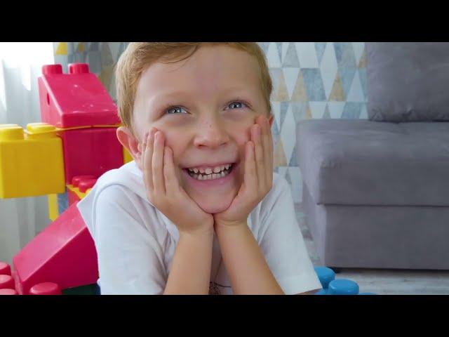 Лёва и папа весело играют с цветными лего блоками, машинками и трактором
