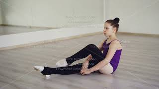Pretty girl choreography student is putting on leg warmers sitting on floor of ballet studio
