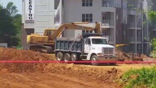John Deere excavator loading Sterling dump truck