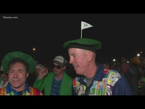 Die-hard golf fans make a mad dash for the 16th Hole at the WMPO