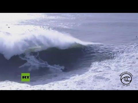 Unha onda enorme leva por diante a un surfeiro en Portugal