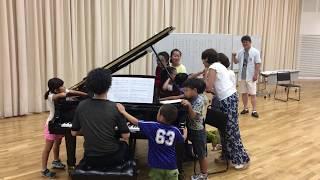 ピアノや喉に触れて響きを確かめる子ども達(東京ホワイトハンドコーラス)