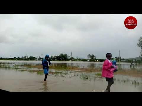 Primary School children wade through flooded road following heavy rains in Migori