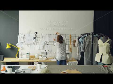 Back view of creative female tailor taking sketches from tailoring desk and hanging them on wall