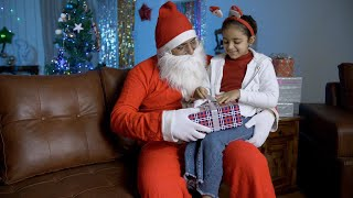 Happy Santa Claus giving a colorful gift box to a young cute child on Christmas in India