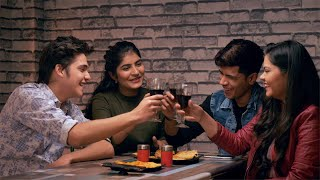 A group of four young teenagers raising a toast to their beautiful friendship in a cafe