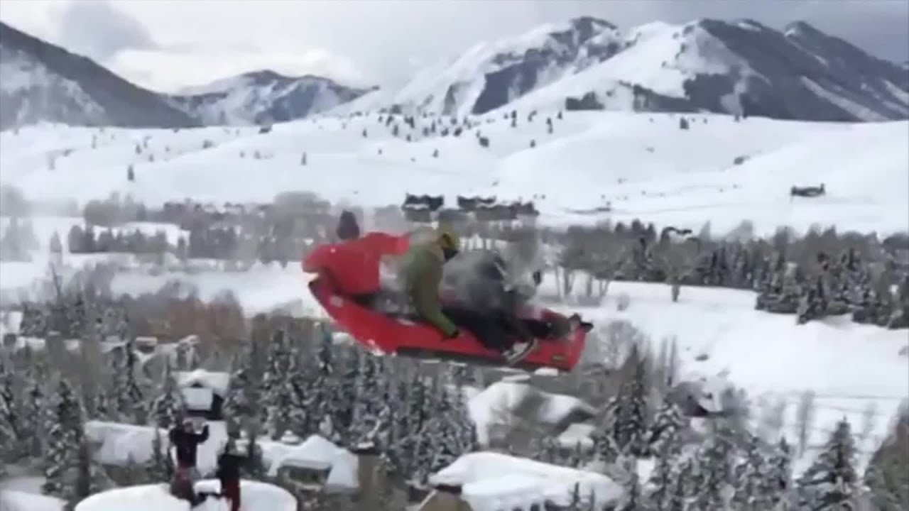 Friends ride inflatable kayak down ski slope