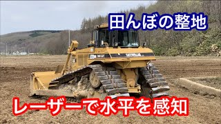 レーザーを利用して水平に均しながら、CATのブルドーザーが田んぼとなる...
