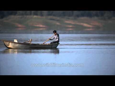 Boy rows a wooden boat on Denwa River in Satpura, MP