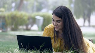 Young beautiful woman lying in a garden while using her laptop - modern lifestyle